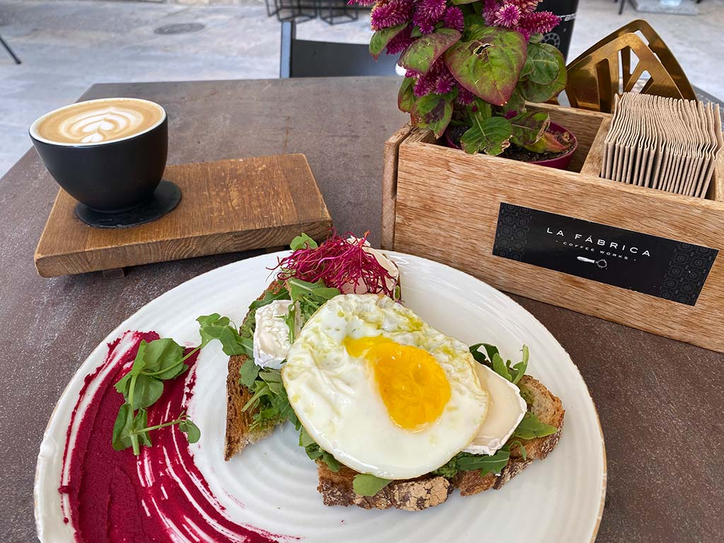 Breakfast at La Fabrica on a Day Trip from Barcelona to Girona - Sourdough bread topped with argula, pesto and eggs